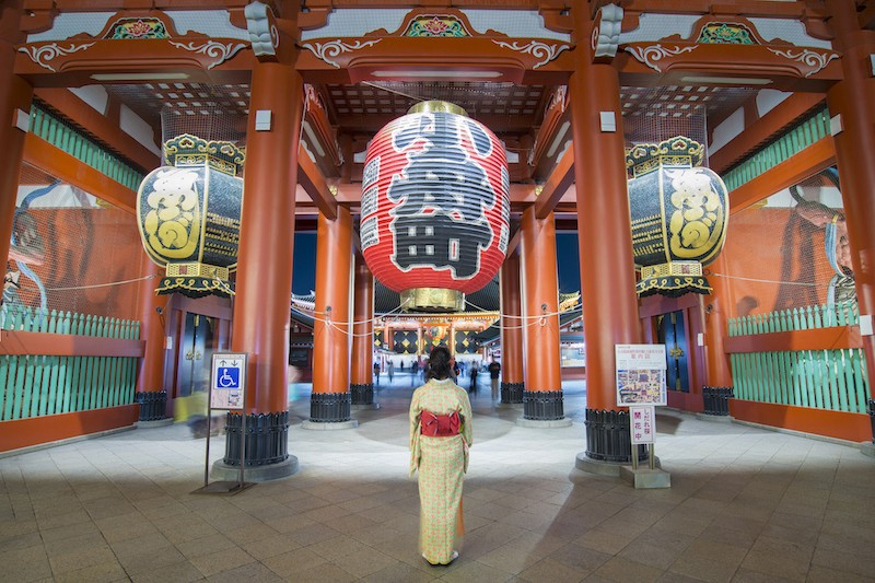 A woman in a kimono stands in front of Asakusa's Kaminarimon gate in Tokyo