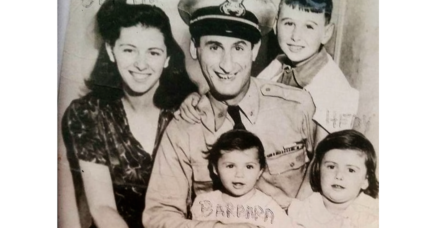Isadore Greenbaum siting for the photo and wearing is petty officer uniform with is wife and three children, four years after the Nazi rally at the Madison Square Garden in New York.