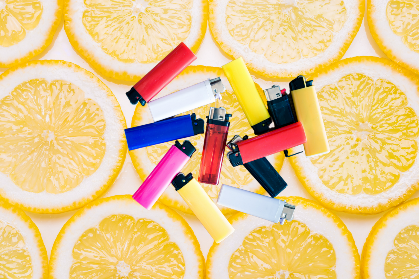 Several lighters against a background of sliced oranges.