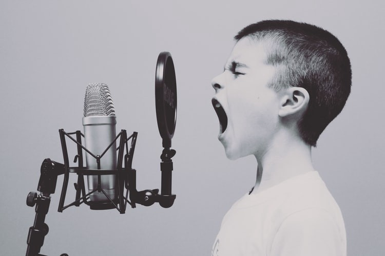 Image of a boy in front of a recording mic, shouting out loud