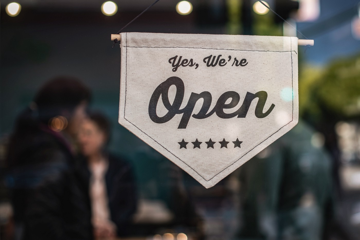 """Tan sign that says """"yes, we're open"""" in front of a blurred background."""
