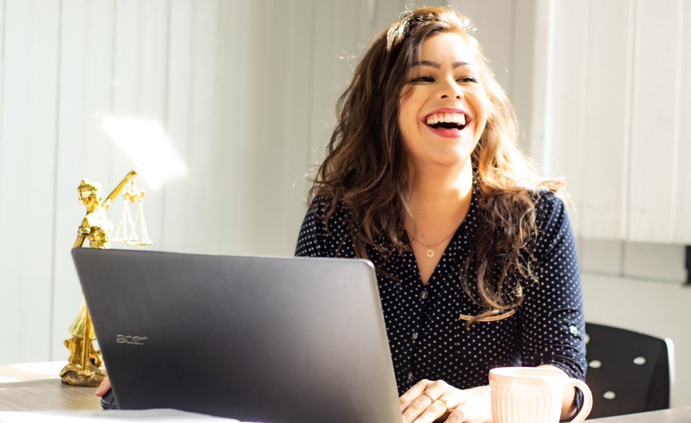A woman laughs while sitting at her desk with a laptop.