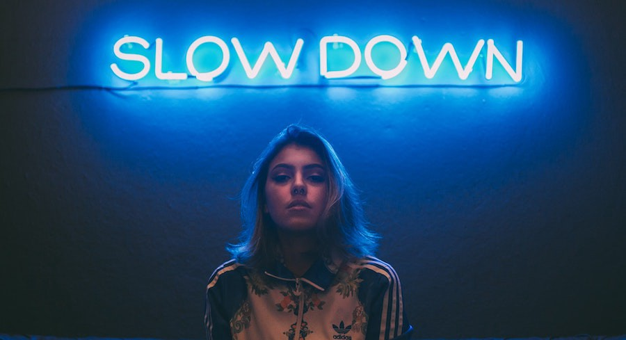 """Neon sign """"Slow Down"""" and young lady underneath"""