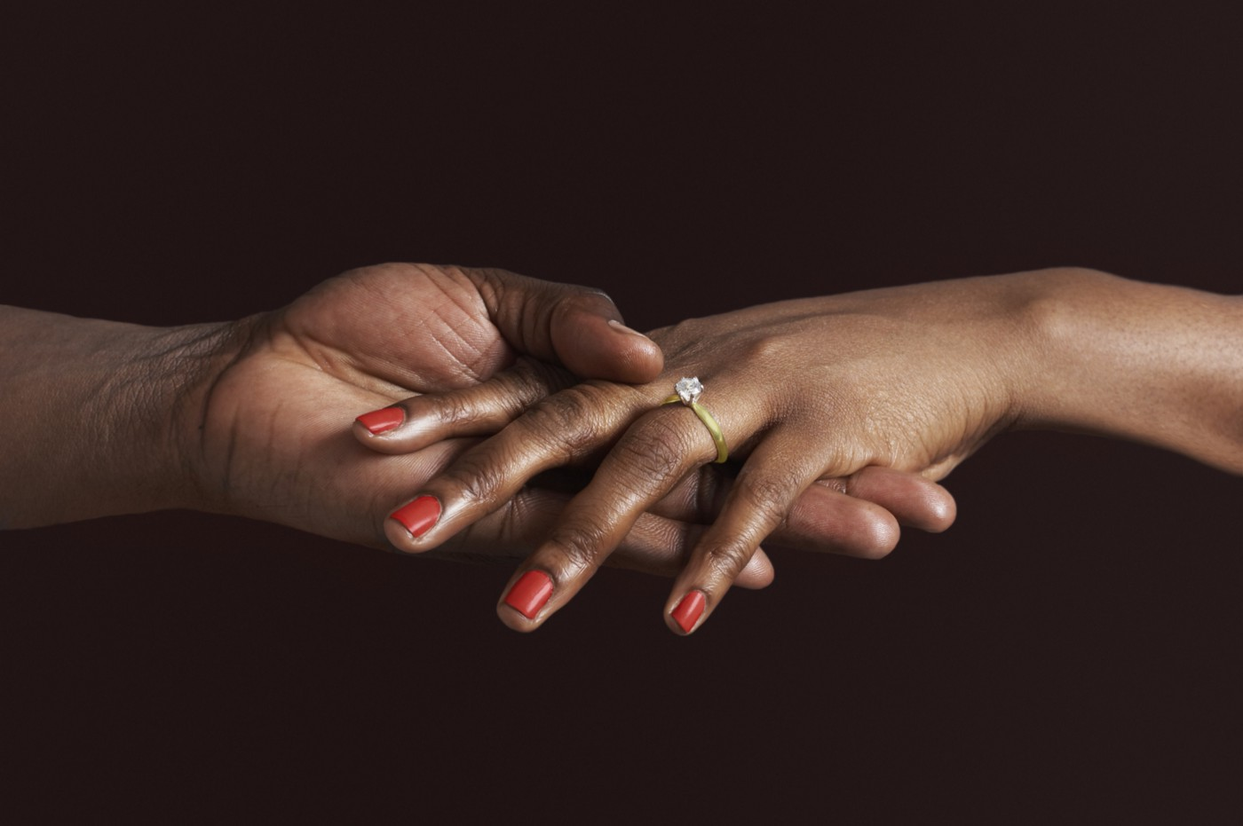 Closeup of a Black woman's hand with an engagement ring.