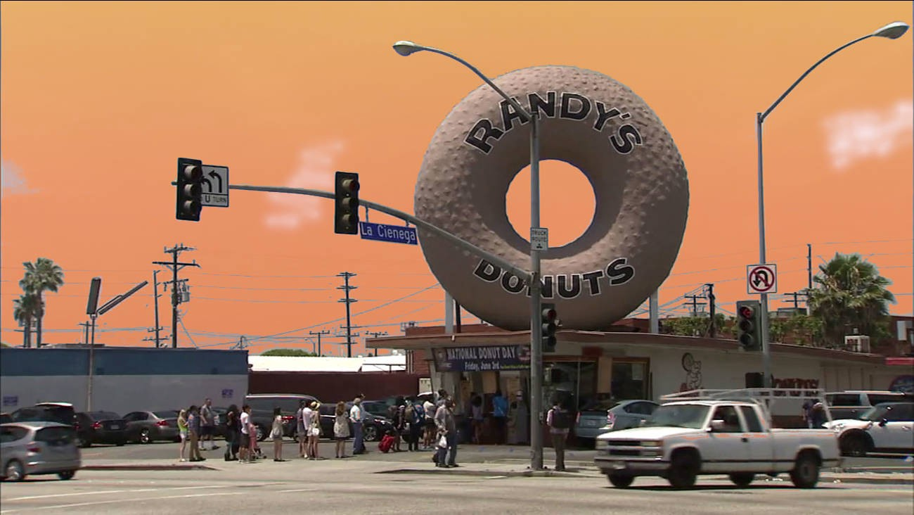A photograph of Randy's Donuts in Los Angeles, California with the torus-shaped donut on top of the shop. People wait in line at a busy intersection. Orange sky.