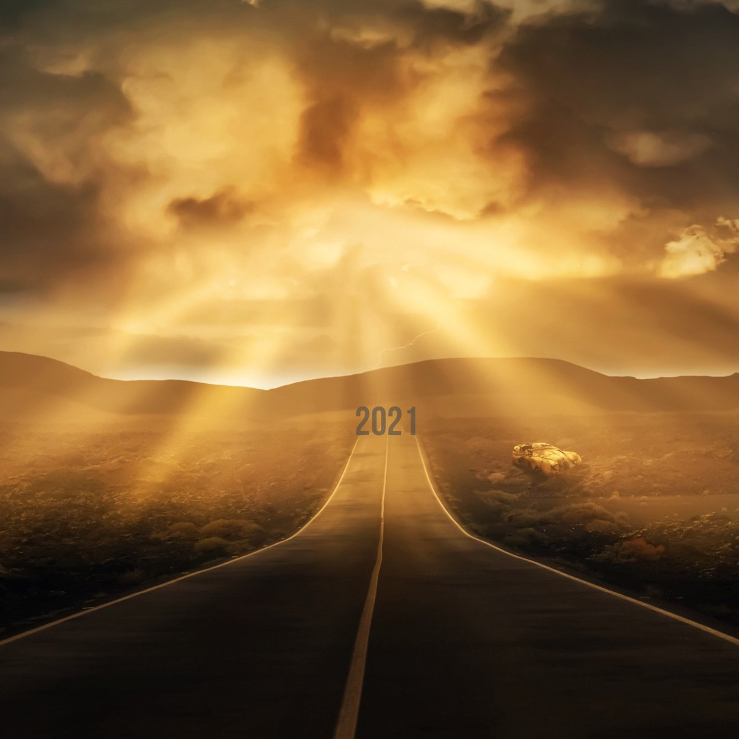 Two way road on the horizon with sunlight shining from cloud and the words 2021 at the end of the road.