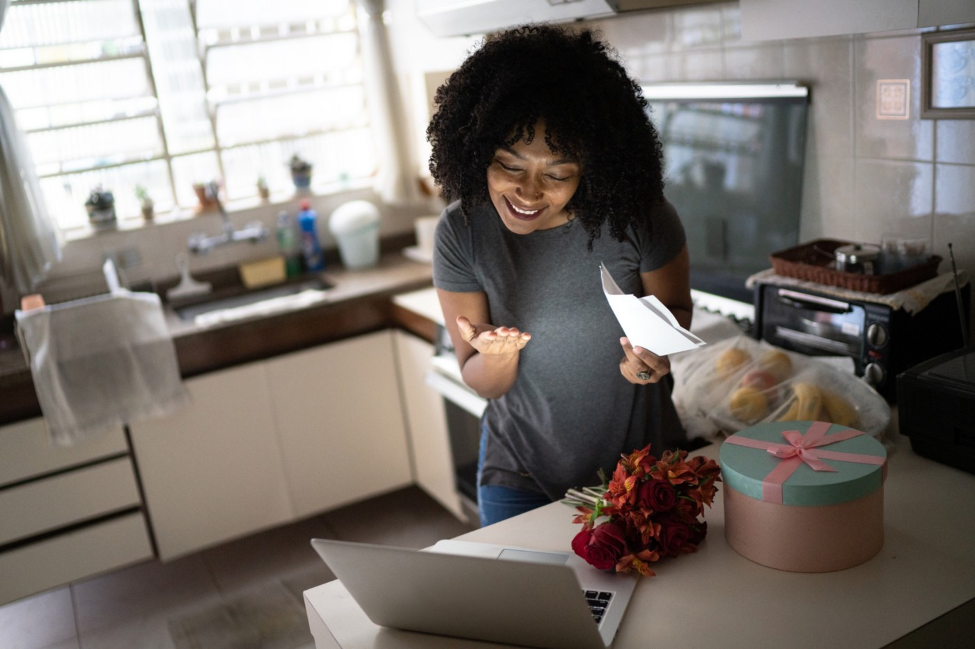 A photo of woman receiving flowers / present in the mail and talking to lover over a video call.