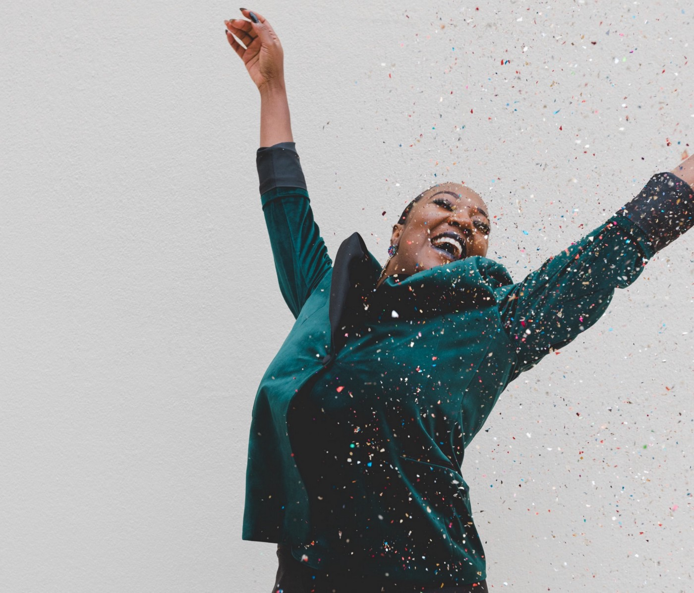 woman jumping for joy with confetti