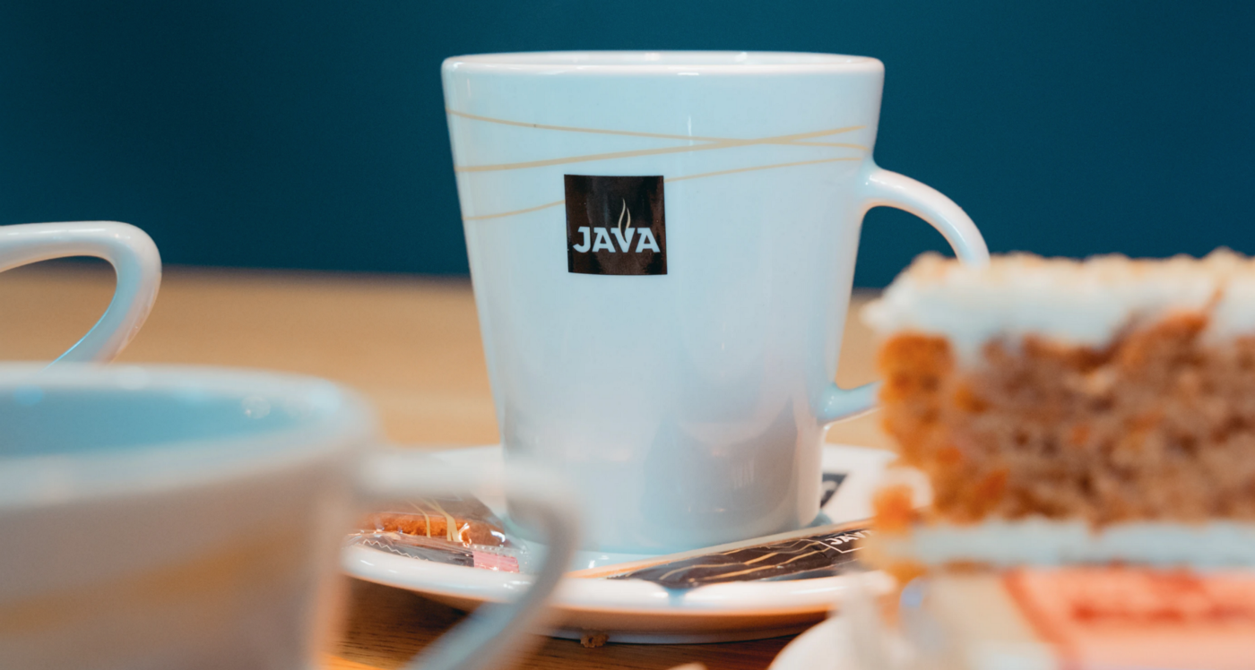 """A cup of coffee with a logo saying """"Java""""."""