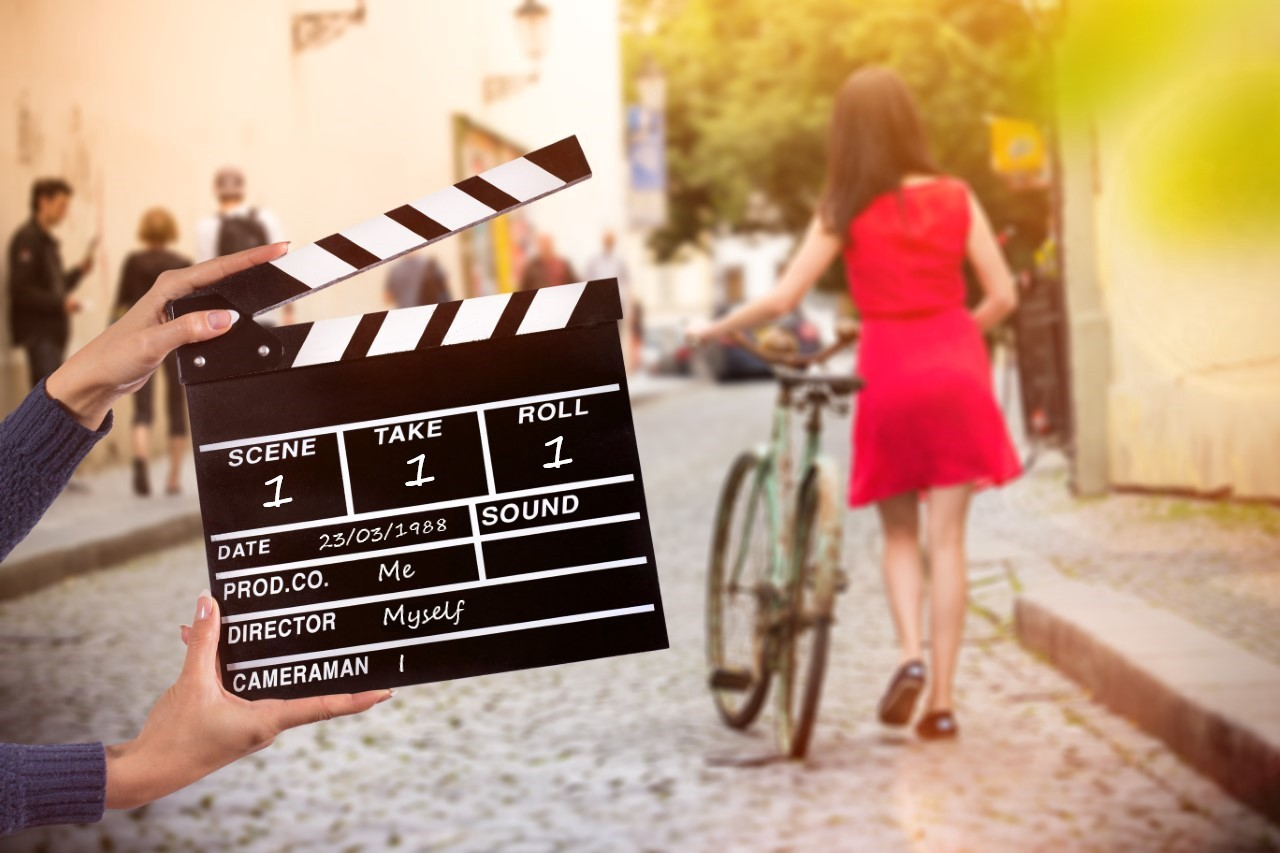 Movie clapper board in front of a scene being shot.