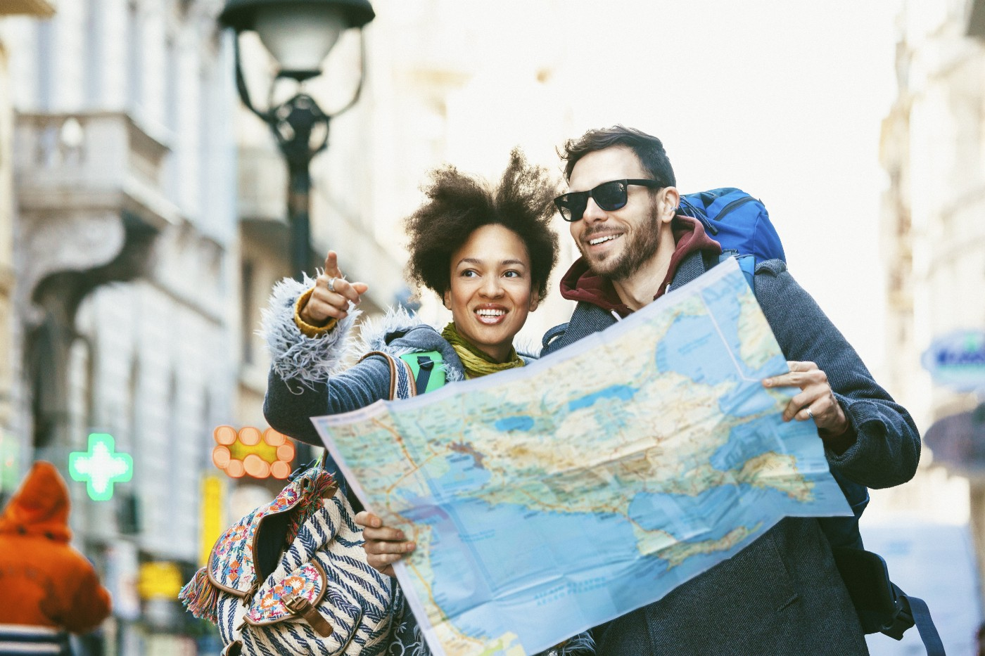 Stock photo of a young couple traveling and holding a map