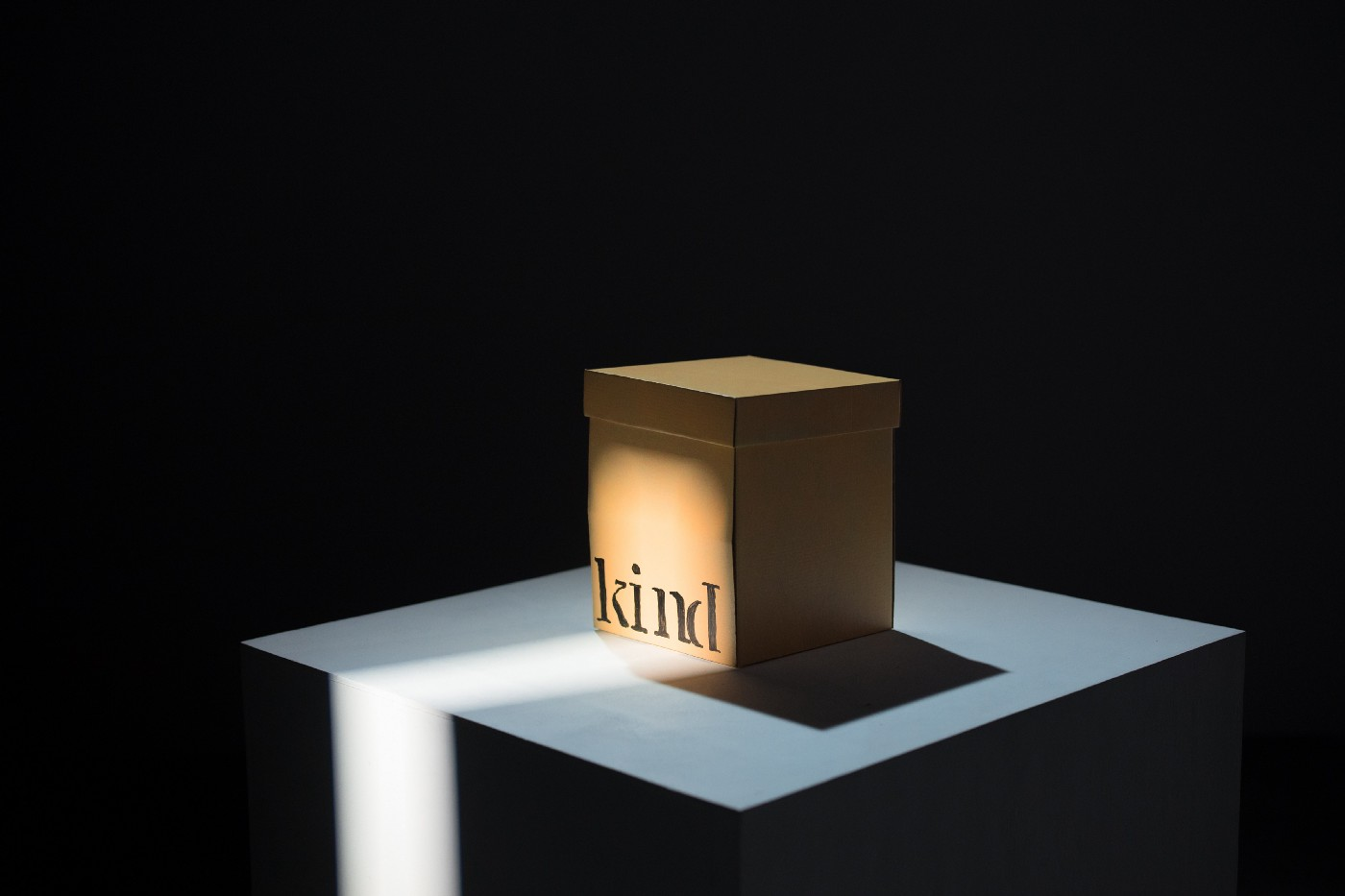 Square brown paper box sitting on a square surface. The box sits in a gleam of light and has the word 'kind' written on it.