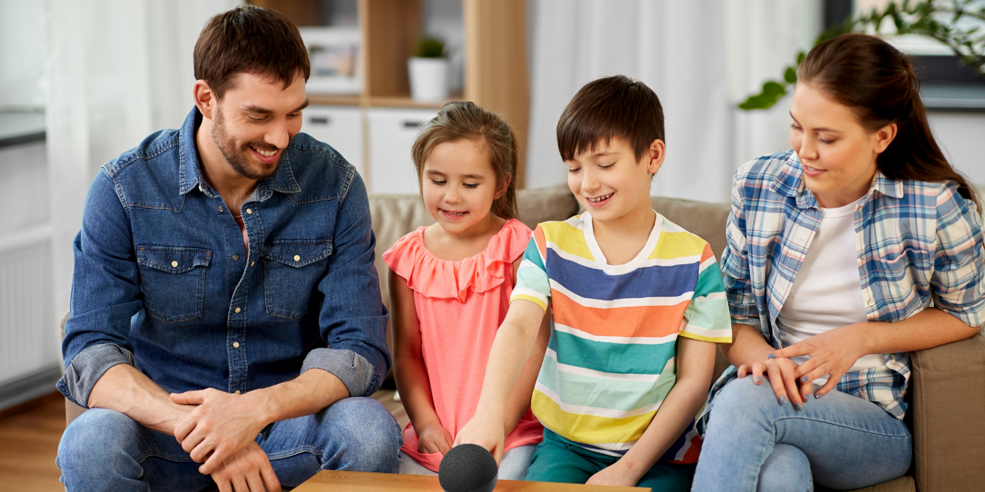 A man, a woman, a girl, and a boy all sat on sofa and looking at an Amazon Echo device