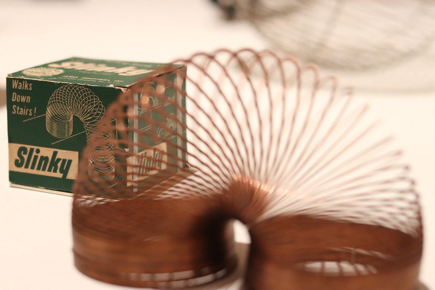 The vintage Slinky box with a partially blurred Slinky fanned out in the foreground.