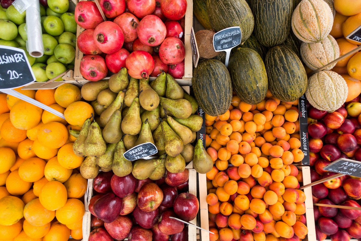 Picture of various fruits in bins at a market: apples, oranges, pomegranates, etc.