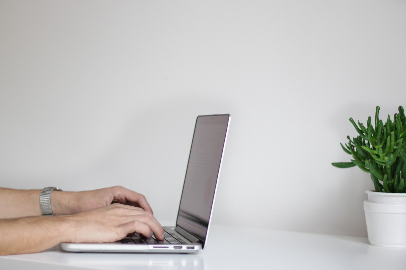 A person on his laptop, writing an article.