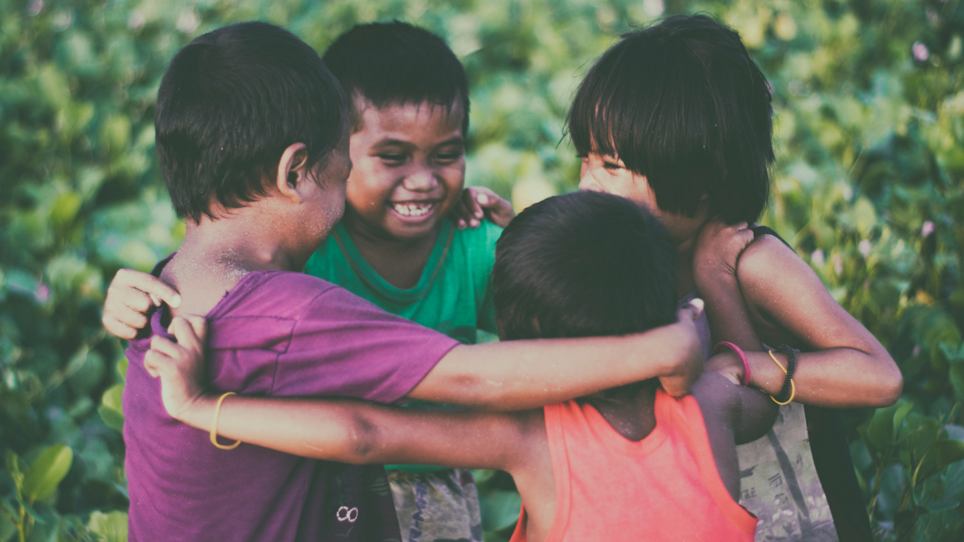 Four children stand in circle with their arms around one another. They have big, joyful smiles on their faces.