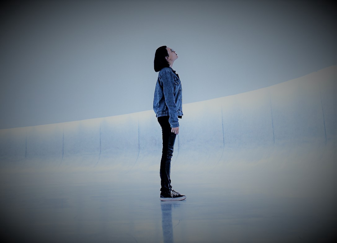 Figure standing in a room and looking upwards