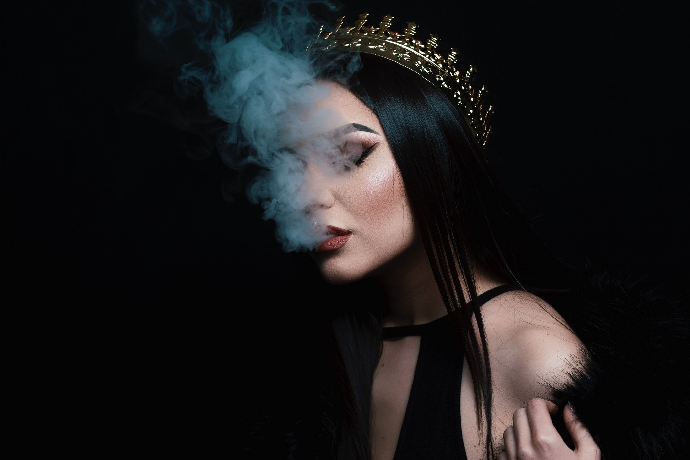 Sophisticated woman wears black formal dress and crown on sleek black hair. She wears dramatic, immaculate makeup. Smoke rises from her mouth.