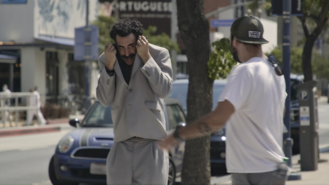 Borat walking past someone on the street and trying to shield his face from them using his suit jacket.