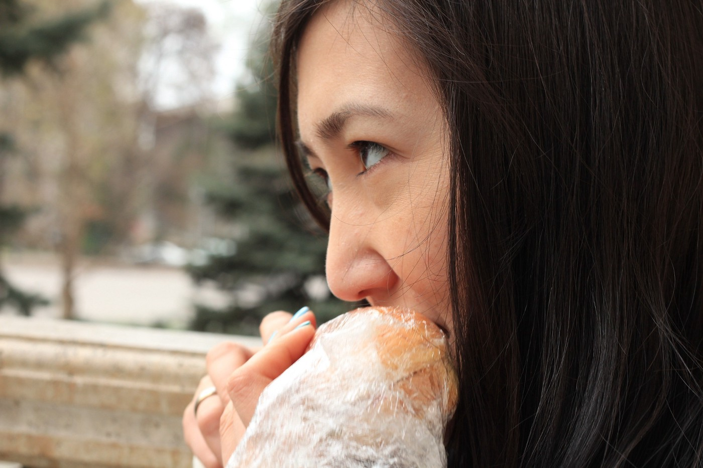 A white woman with dark hair eating a sandwich outdoors