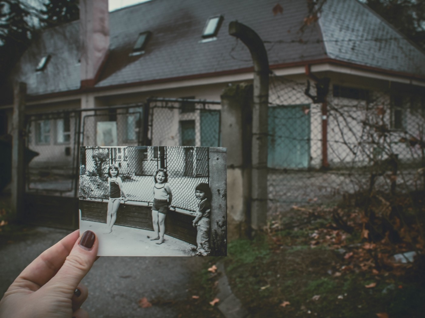 An old photo is held up in front of the building where it was taken a long time ago.
