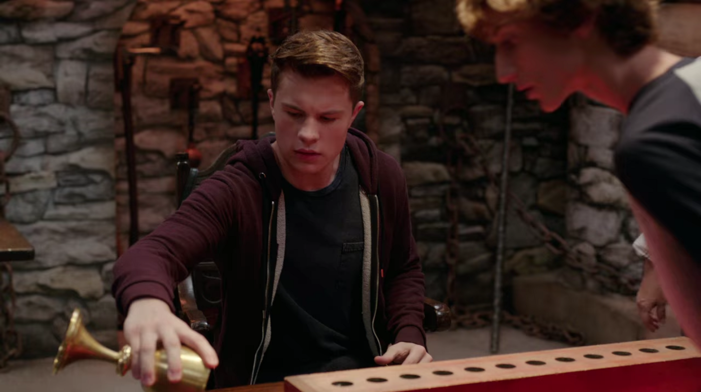A white teen boy sits at a table in a medieval-themed room. He's pouring something out of a golden chalice onto the surface of a table, where there's also a long plank of wood with holes in a line across it.