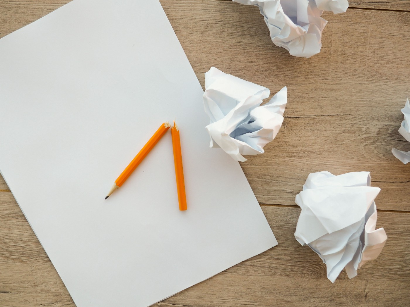 the image shows a plain piece of paper alongside a broken pencil and 4 balls of scrumpled-up paper