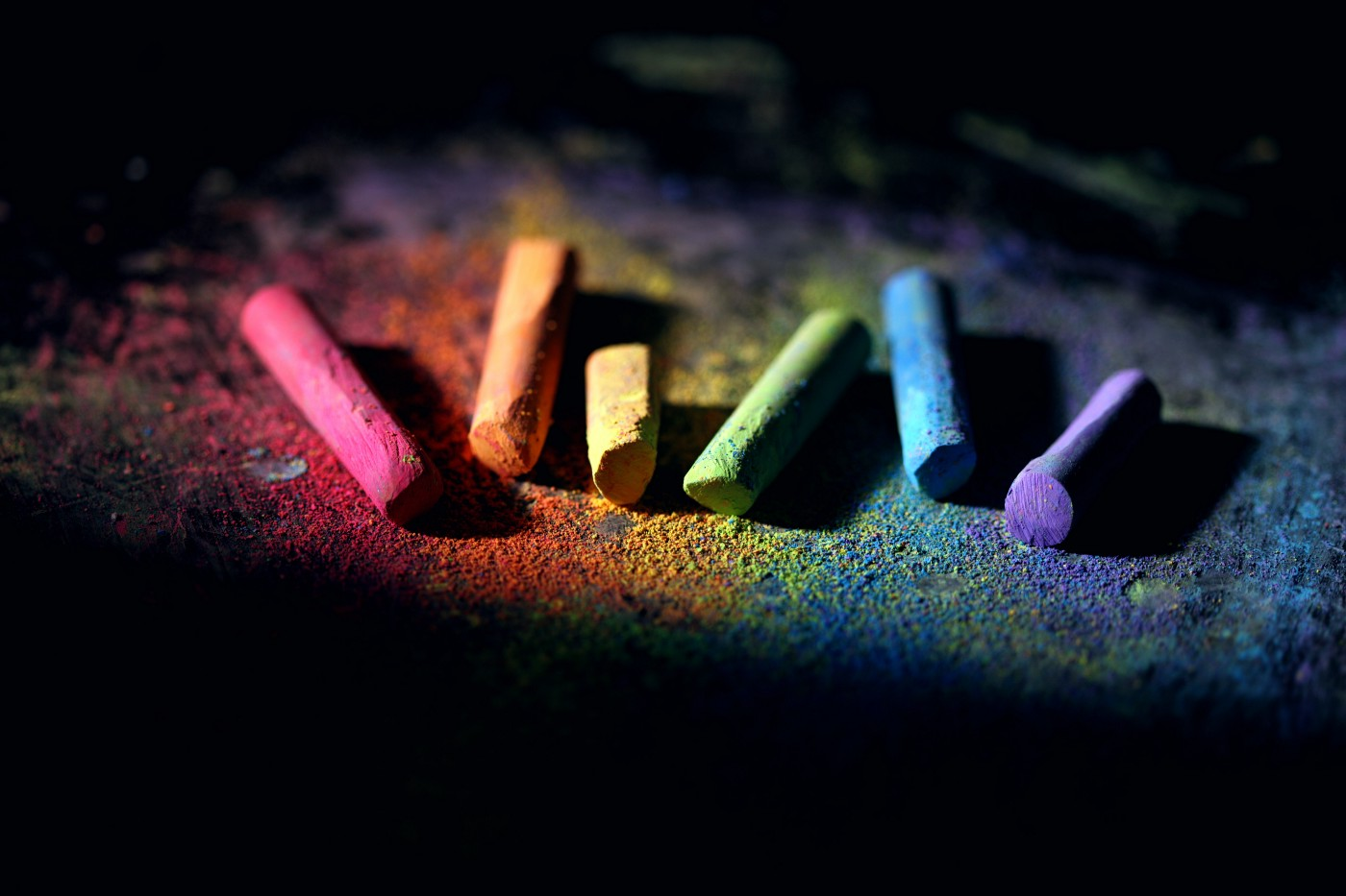 A rainbow of coloured chalk against a black background