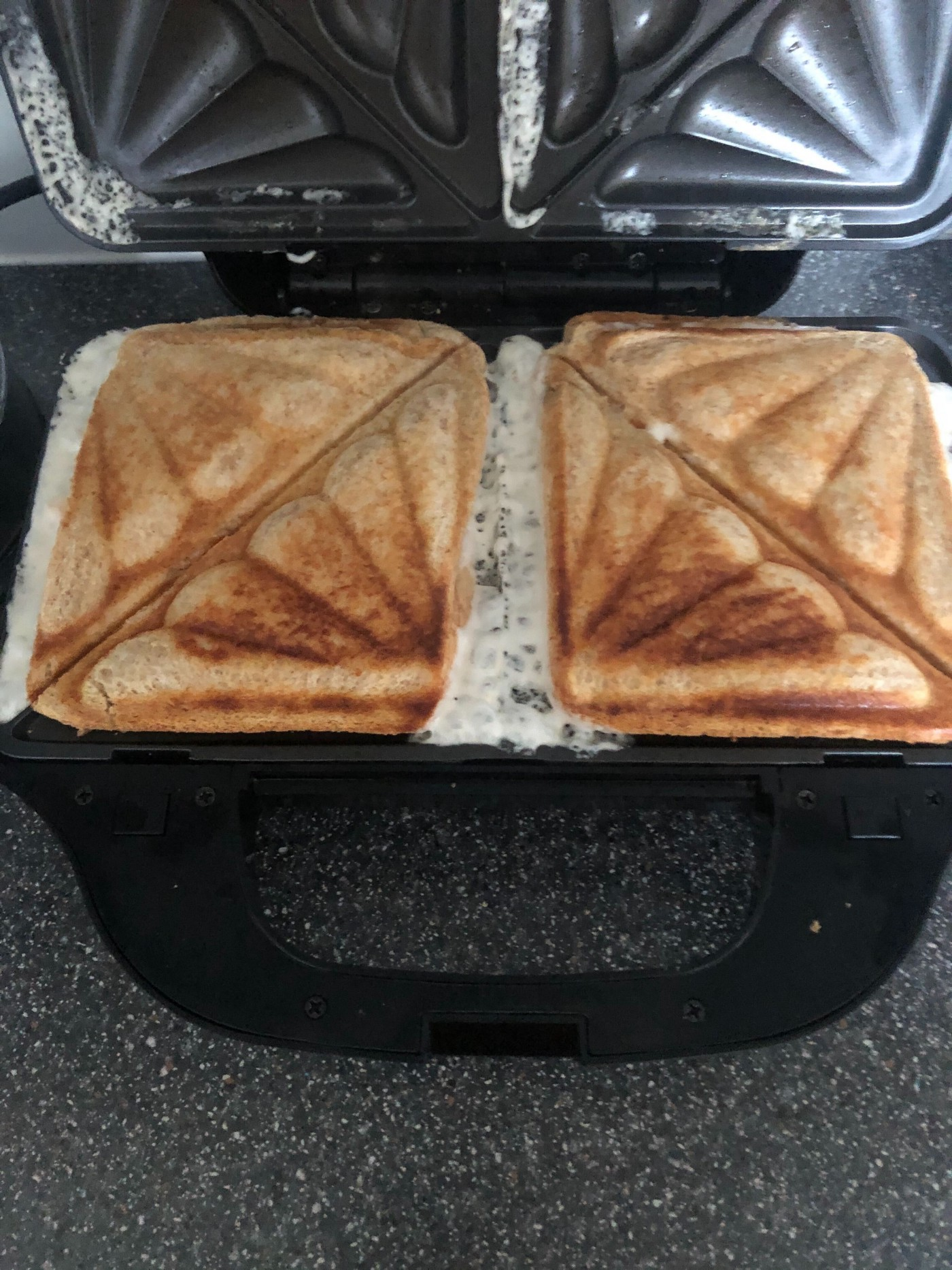 A toastie sandwich machine with two sandwiches leaking the filling all over the machine, leaving a mess.