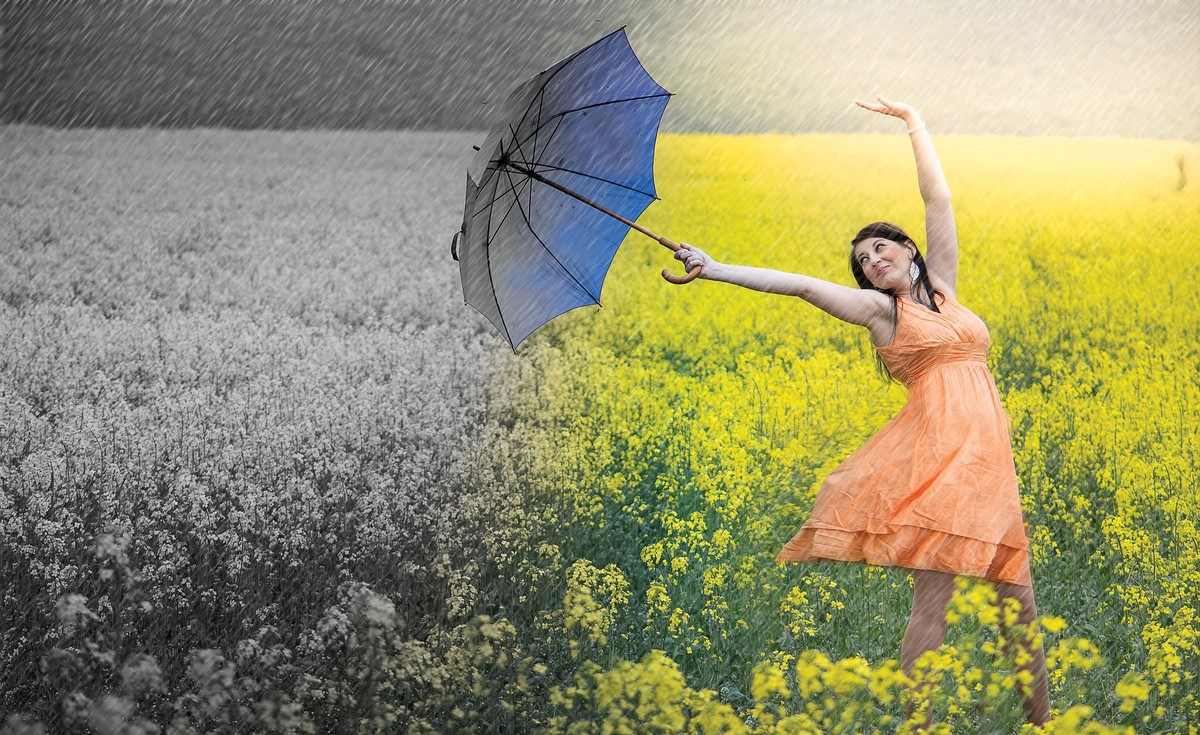 Woman with umbrella moving from dark, cold place into a sunny, warm place with flowers in background