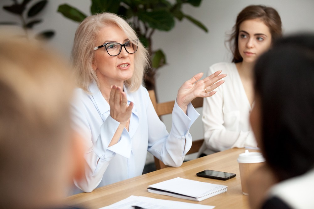 attractive middle aged woman coaching. Shutterstock by Fizkes