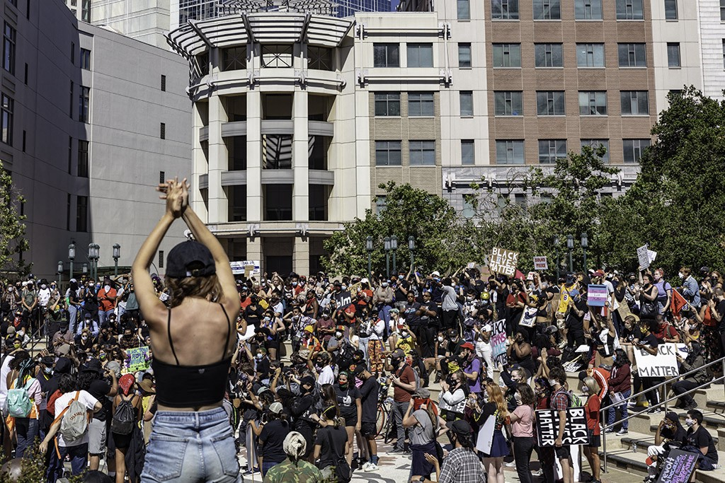 Protestors applaud a speaker at downtown Oakland's Juneteenth 2020 protest