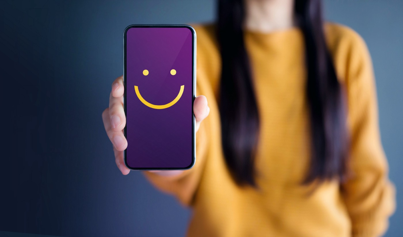 Customer service concept with female client holding up mobile phone with smiley face.