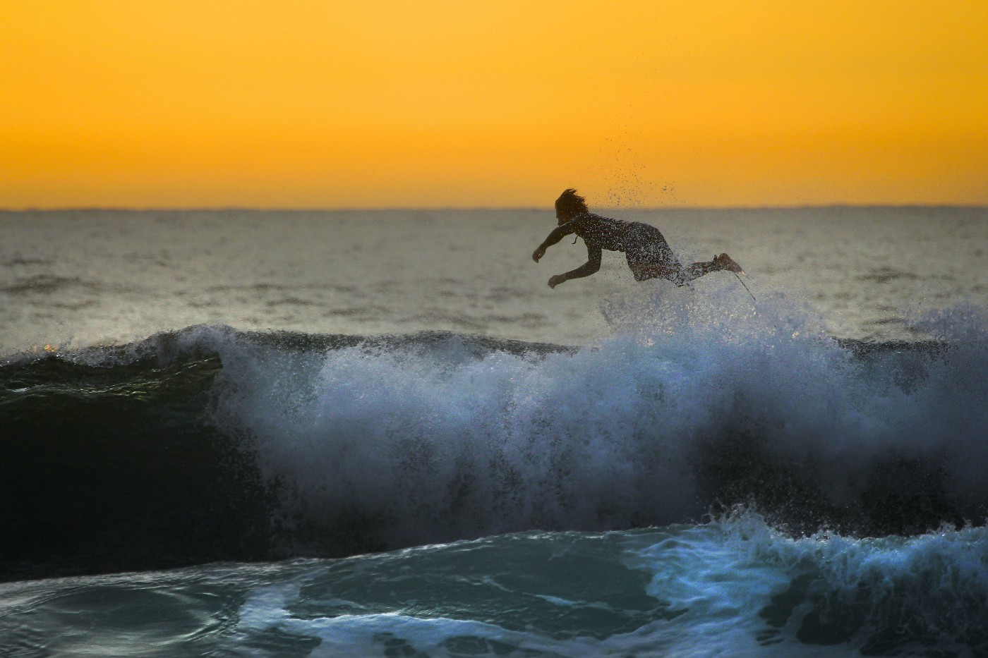 Woman flying off surfboard in the sea