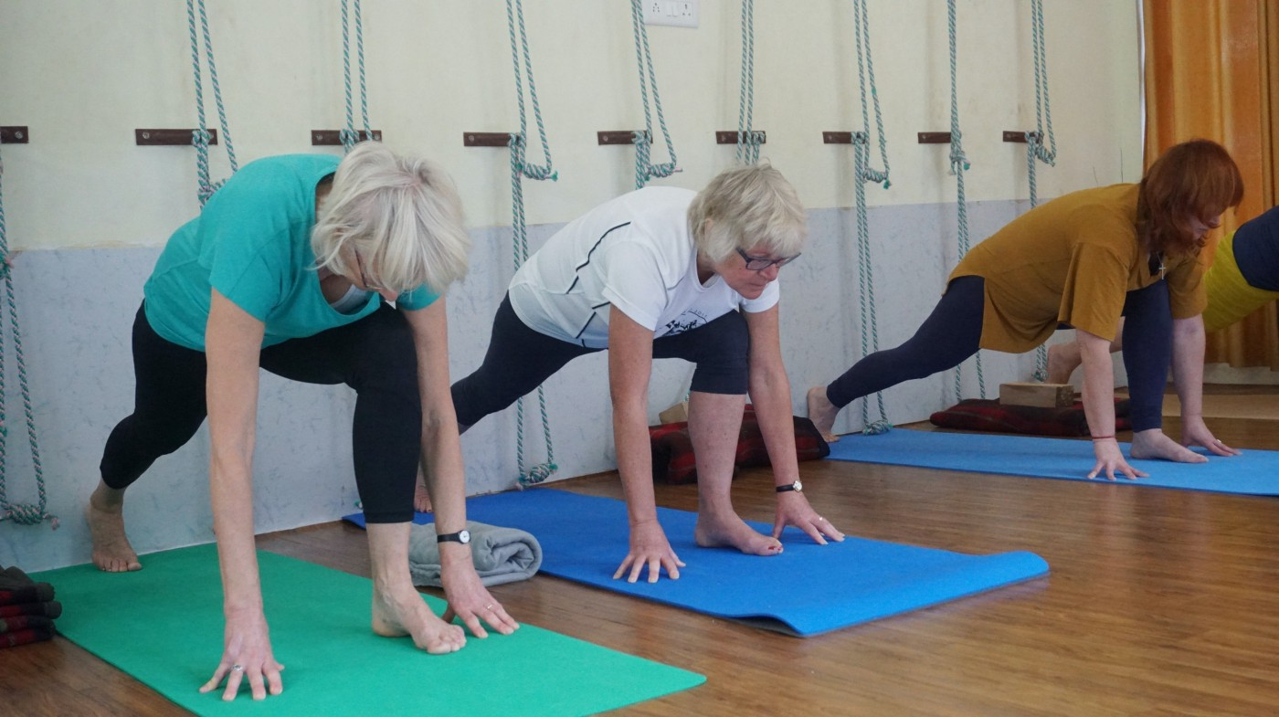 Two women with gray hair and one woman with red hair, all in a low lunge on yoga mats in a yoga studio with a hardwood floor. Behind them are turquoise ropes for assistance in other stretches.