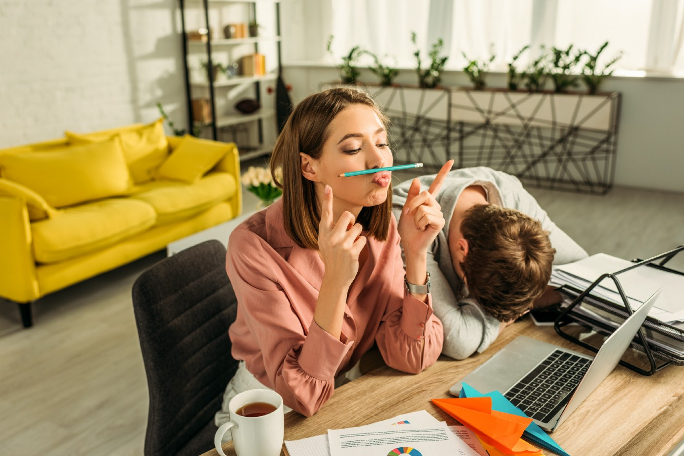 Bored woman at computer with man sleeping on desk next to her.