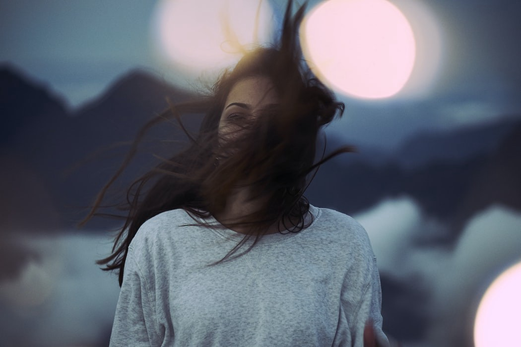 Racially ambiguous female model in gray sweatshirt with long brown hair hiding her face in the wind