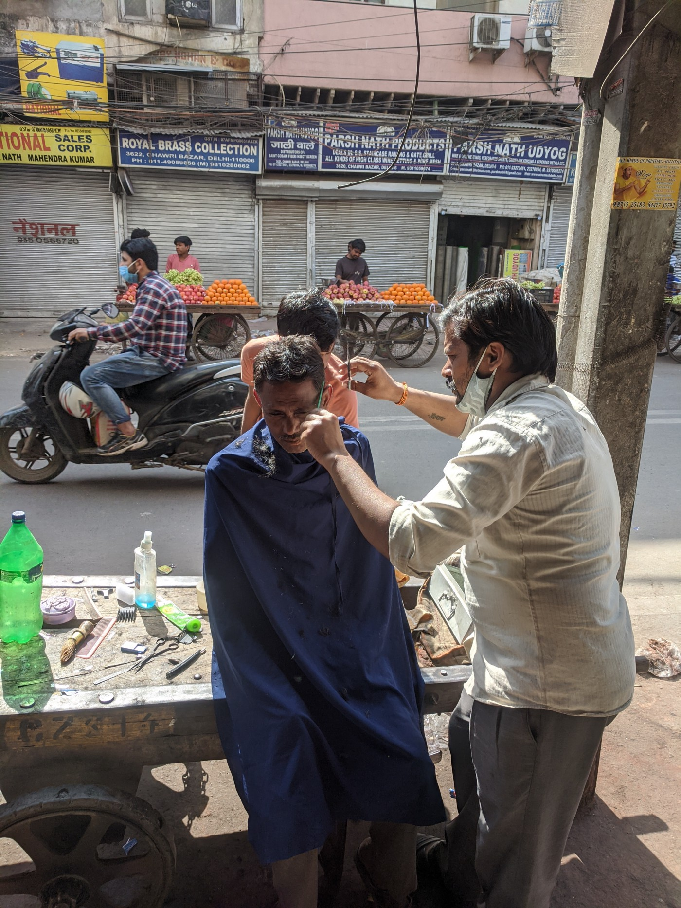 Barber cutting hair in middle of the road in Old Delhi