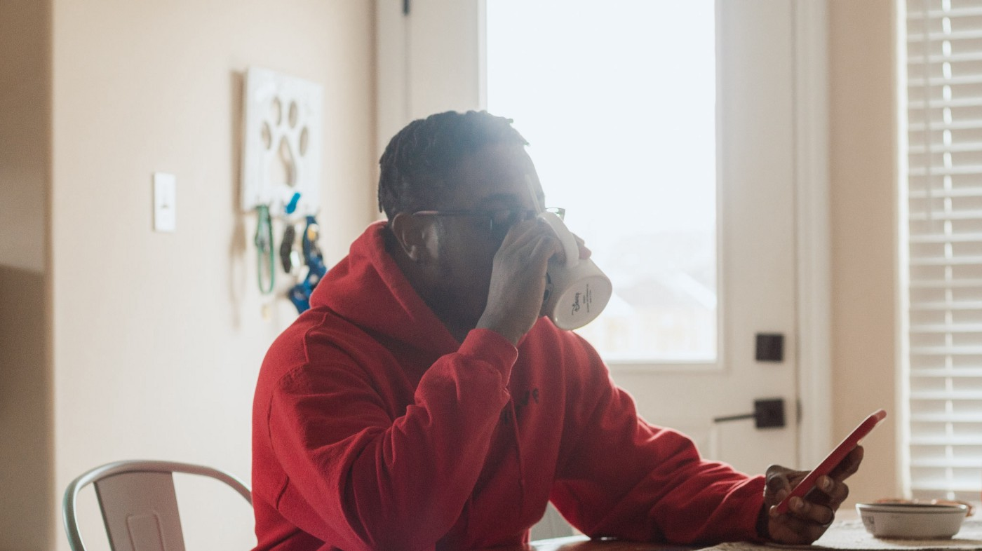 African American male in red hoodie sipping coffee and looking at smart phone.