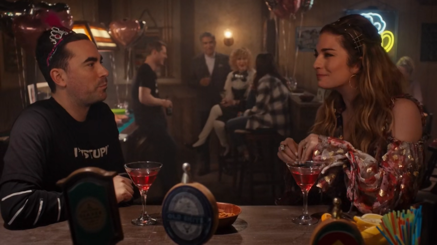 In the foreground, a brother and sister chat at a bar. In the background, two parents and two young people are talking