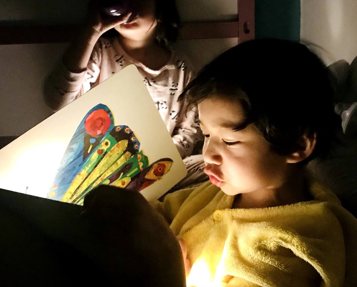 Boy reading The Very Hungry Caterpillar to a girl by flashlight.