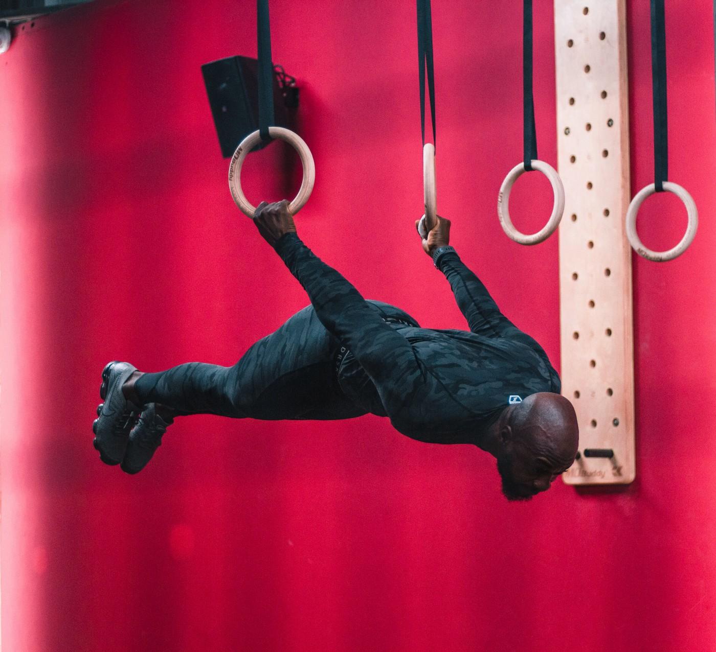 a gymnast hangs from rings in the horizontal position