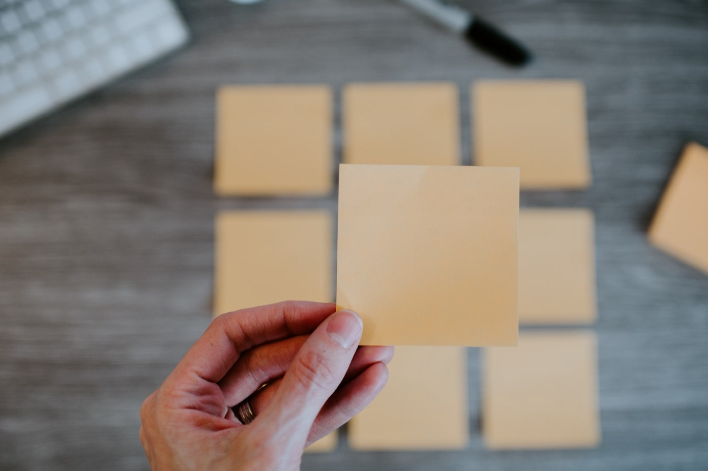 Hand holding a blank post-it