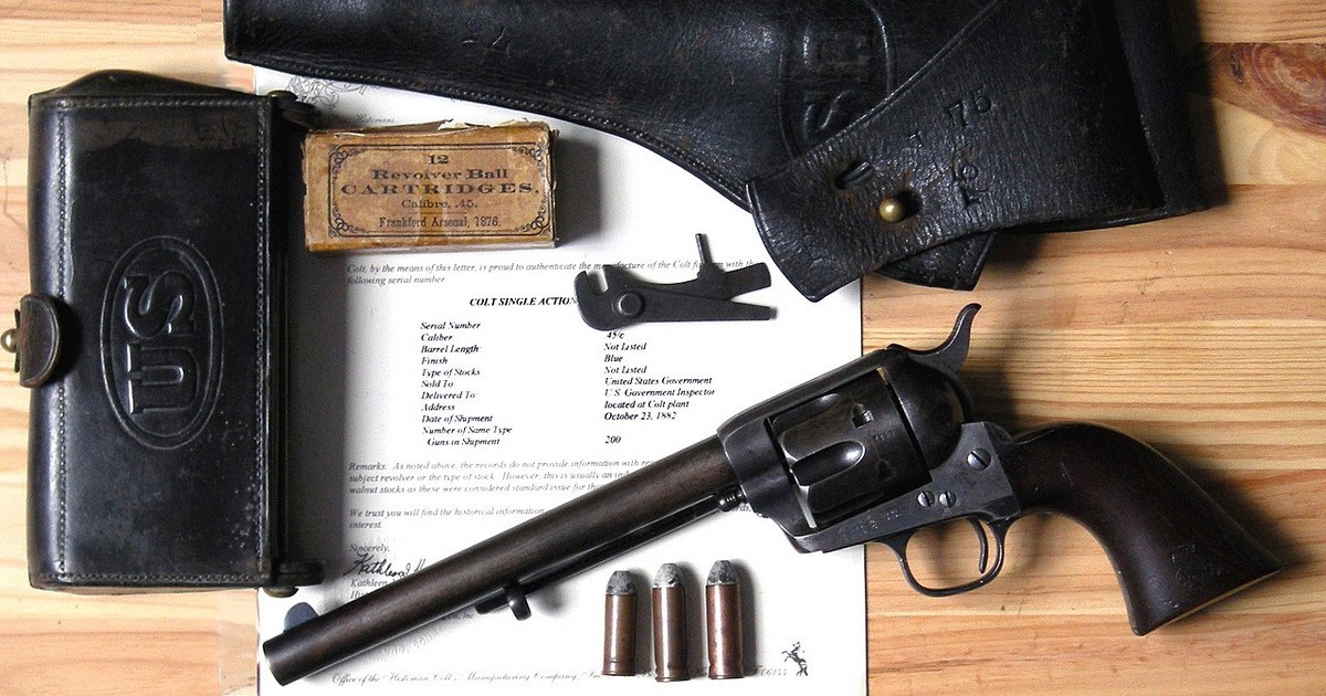 Antique pistol with Army holster and shell pouch on a table atop a letter of authentication from Colt.