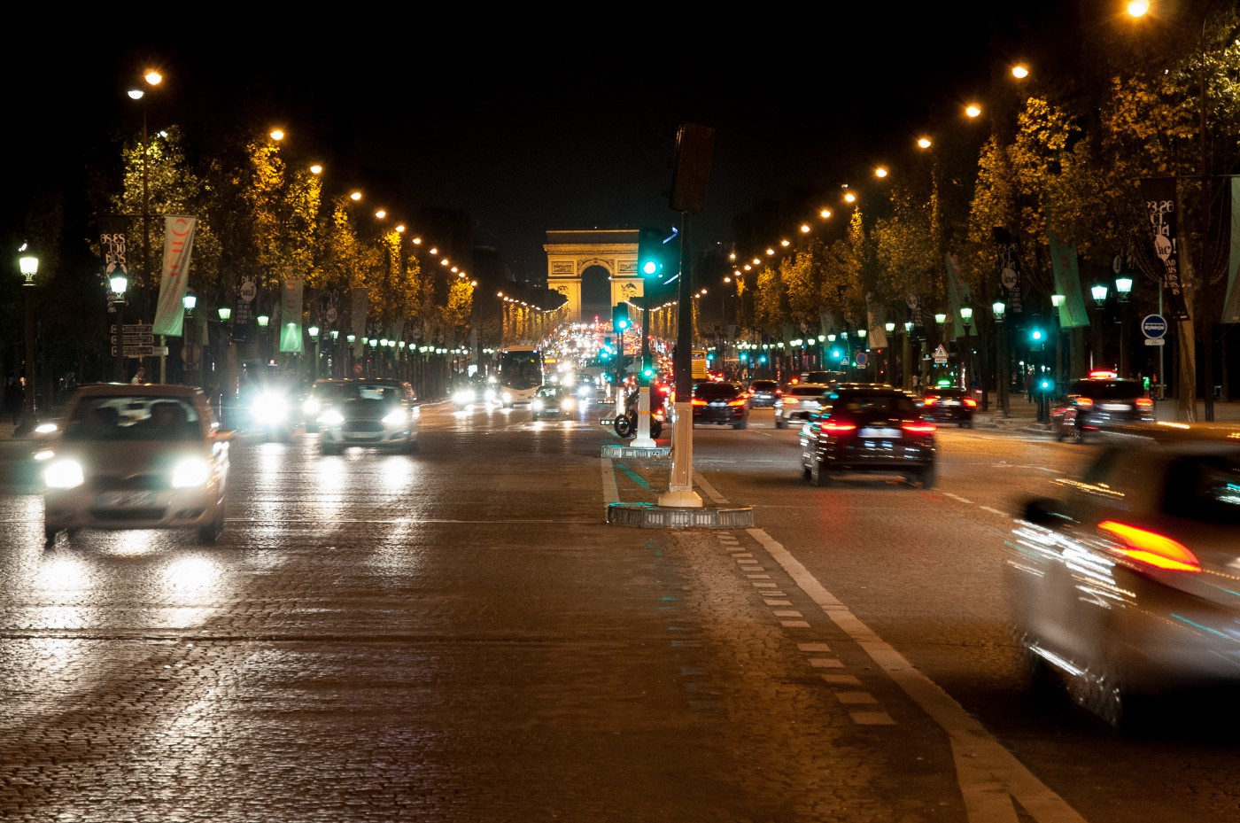 The Champs-Élysées at night, with fast-moving traffic going both ways.