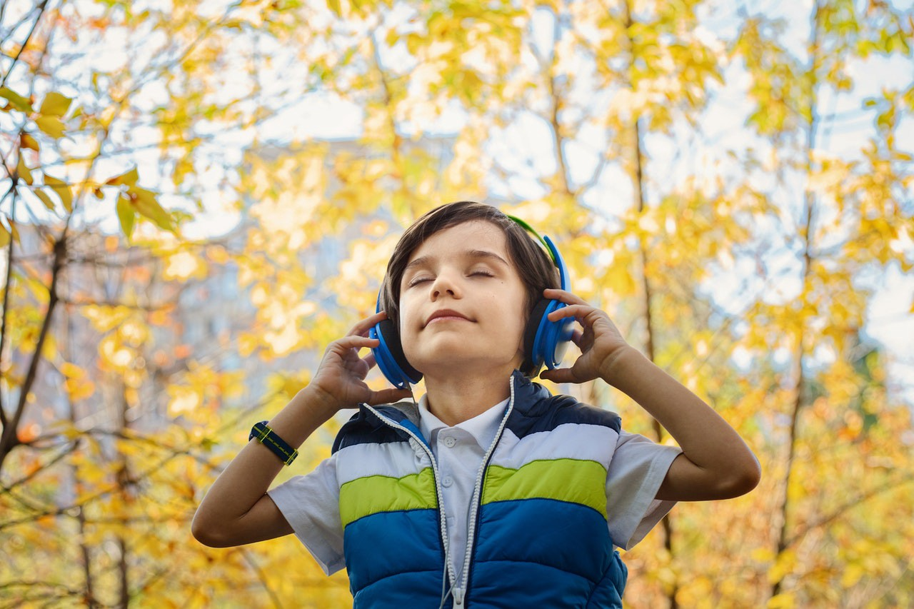 outside autumn scene, boy looking calm with eyes closed and headphones on