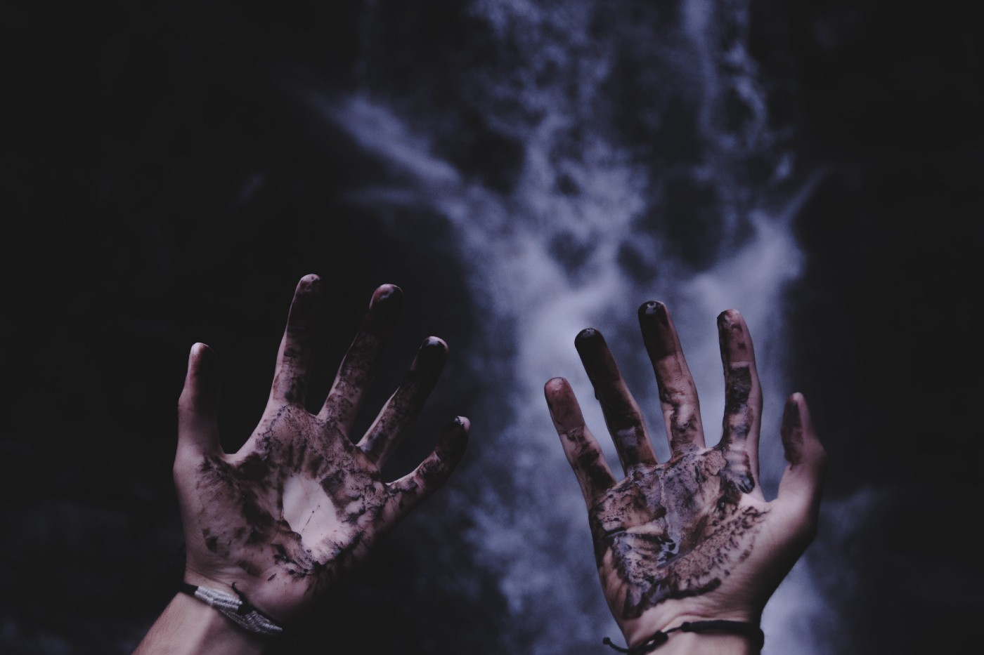 Two hands with palms facing upward with what appears to be a mixture of blood and mud on the hands, behind the hands are a black background with white fog on the background, has an ominus tone to it
