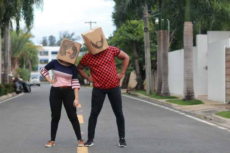 A man and woman couple on a street with paperbags on their heads.
