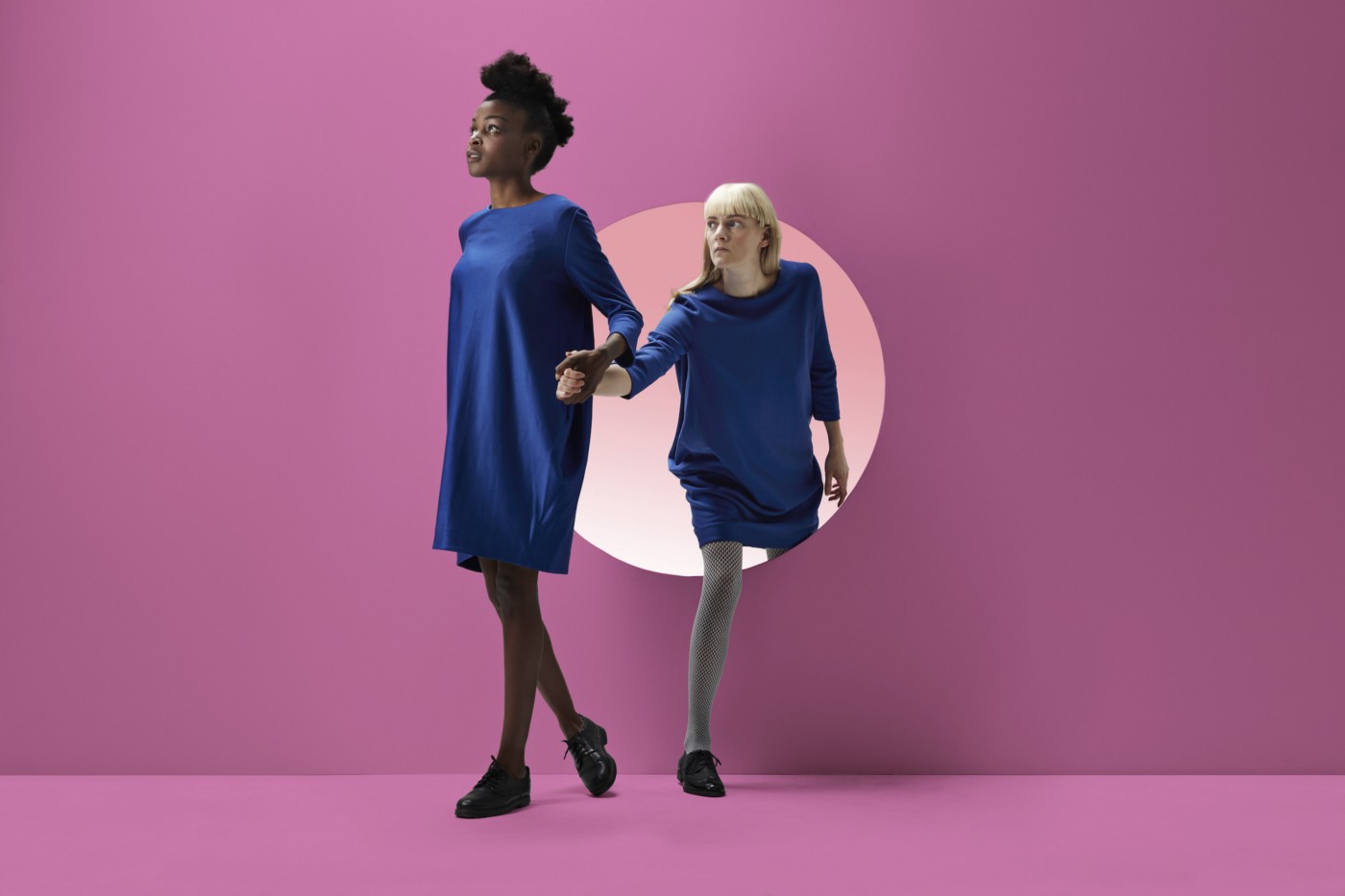 Two women peeking out of round opening in a pink wall.